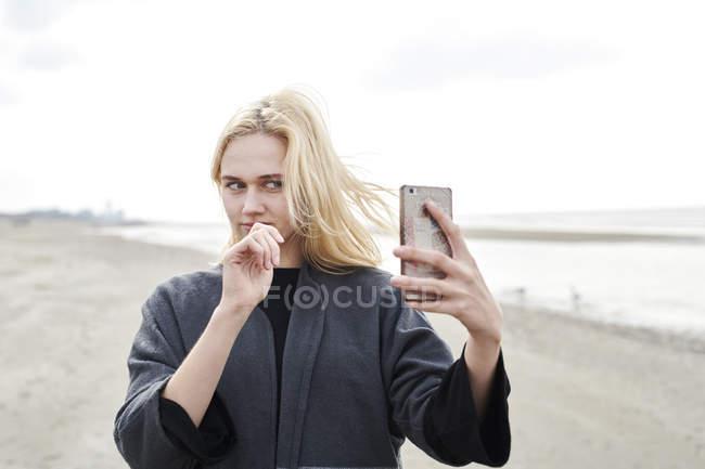 Нідерланди, портрет блондинки молода жінка, що робить селфі з смартфоном на пляжі. — стокове фото