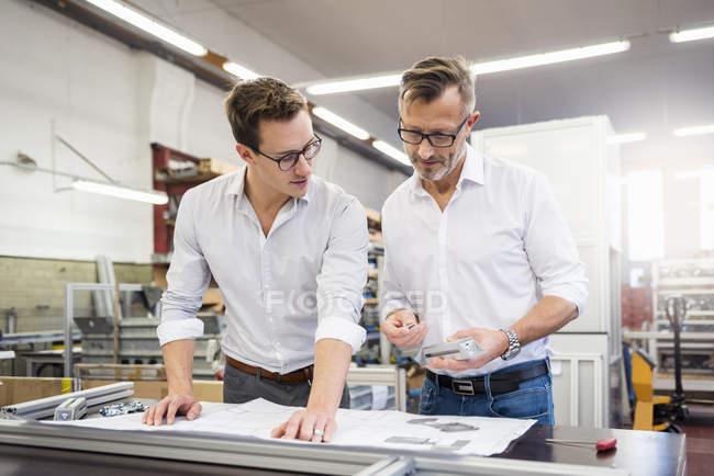 Dos hombres de negocios en la fábrica discutiendo el plan - foto de stock