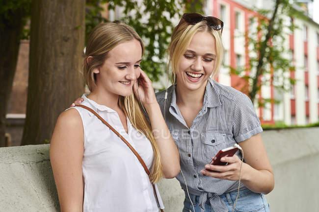 Duas jovens felizes compartilhando telefone celular e fones de ouvido ao ar livre — Fotografia de Stock