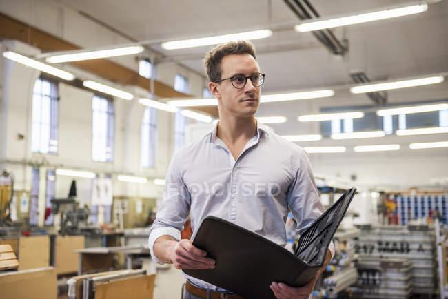 Jungunternehmer in Werkshalle — Stockfoto