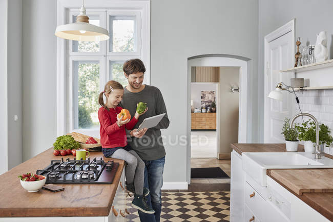 Усміхнений батько і дочка з перцем і планшетом в кухні — стокове фото