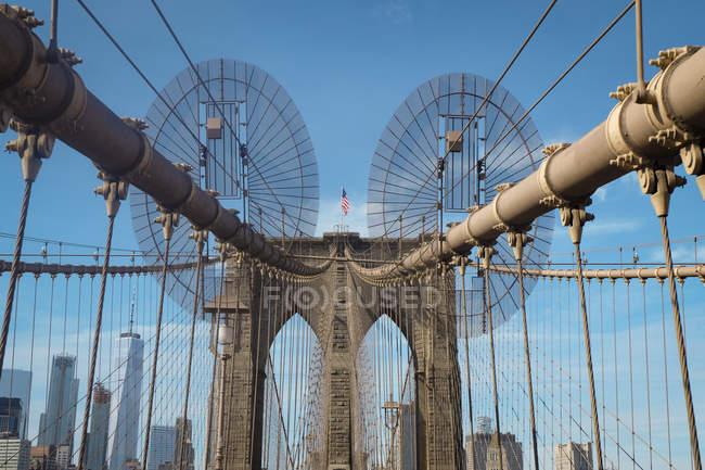 États-Unis, New York, Brooklyn, Gros plan des câbles métalliques du pont de Brooklyn et des arches avec drapeau américain sur le dessus — Photo de stock