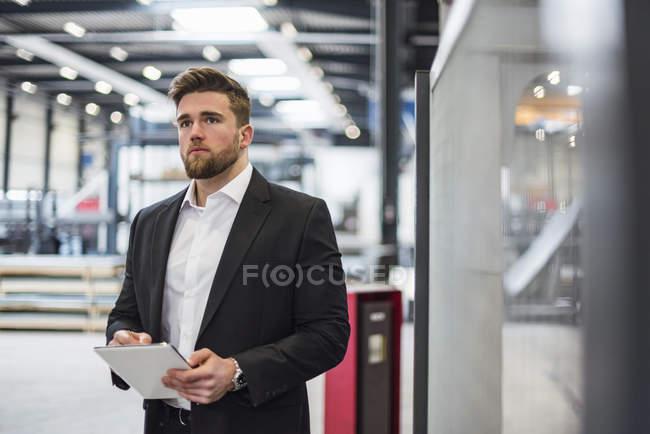 Homme d'affaires utilisant une tablette sur le plancher de l'atelier de l'usine — Photo de stock