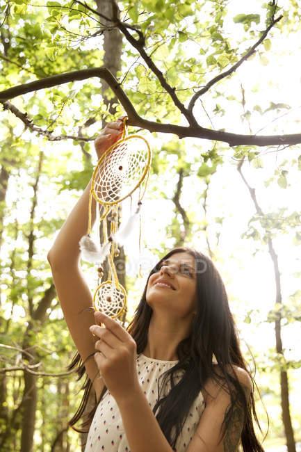 Frau hängt Traumfänger auf Ast eines Baumes — Stockfoto