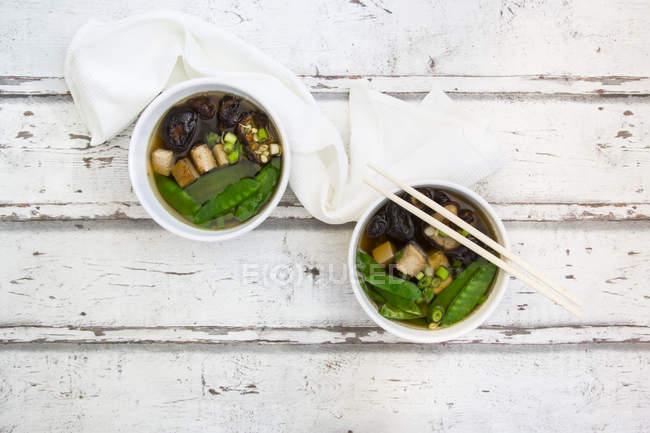 Vista dall'alto della zuppa di miso giapponese con piselli da zucchero, shiitake, tofu e cavoletti mung su superficie di legno — Foto stock