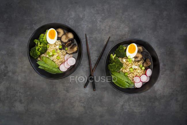 Soupe Ramen avec œufs, pois mange-tout, brocoli, nouilles, champignons shitake et radis rouge — Photo de stock