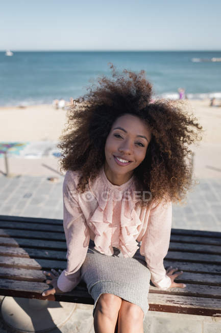 Portrait of smiling beautiful young woman with afro hairdo sitting on a bench at the beach — Stock Photo