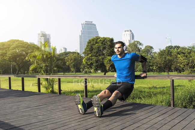 Runner con cuffie che fanno flessioni nel parco urbano — Foto stock