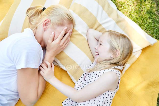 Glückliches Mädchen mit Mutter auf Decke liegend — Stockfoto