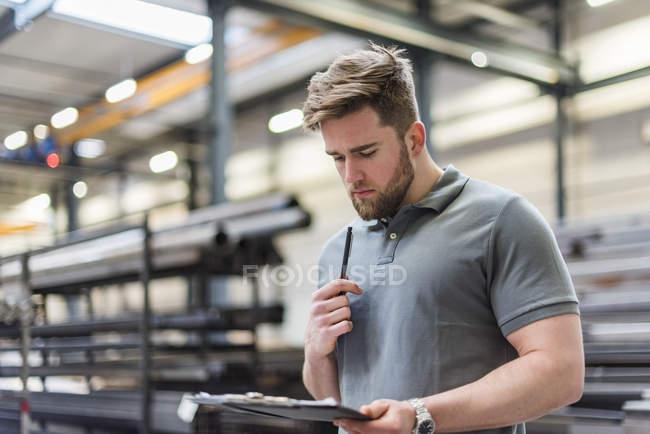 Mann schreibt auf Zwischenablage in DerFabrik — Stockfoto