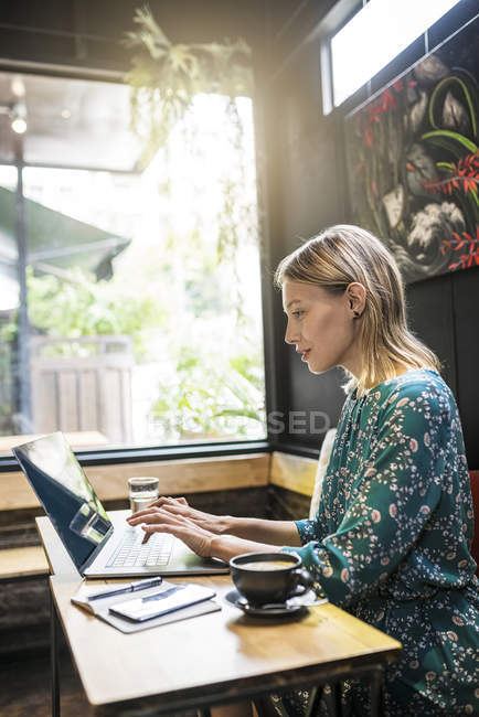 Young woman with green dress sitting in cafe, working on her laptop — Stockfoto