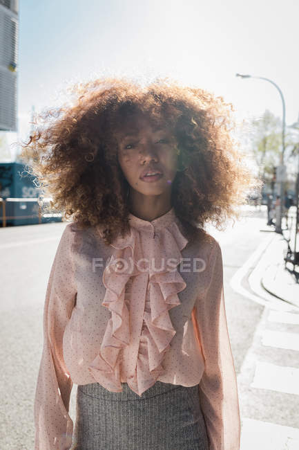 Portrait of beautiful young woman with afro hairdo in the city — Stock Photo