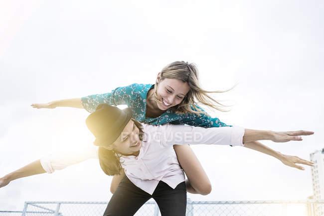 Jeune couple affectueux s'amuser ensemble sur le toit, prétendant voler — Photo de stock