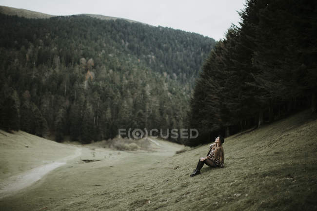 Young woman sitting on a meadow near forest edge and looking up — Stock Photo