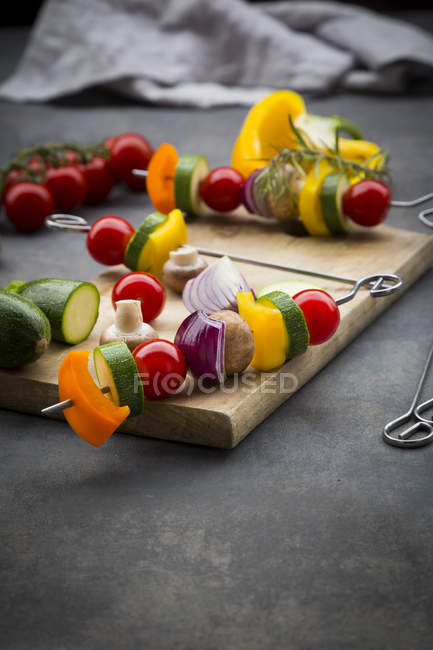 Raw vegetarian grill skewers on wooden board — Stock Photo