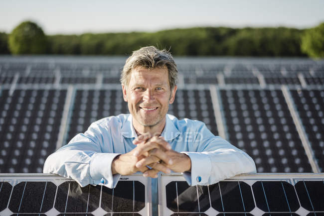 Smiling mature man standing in solar plant — Foto stock