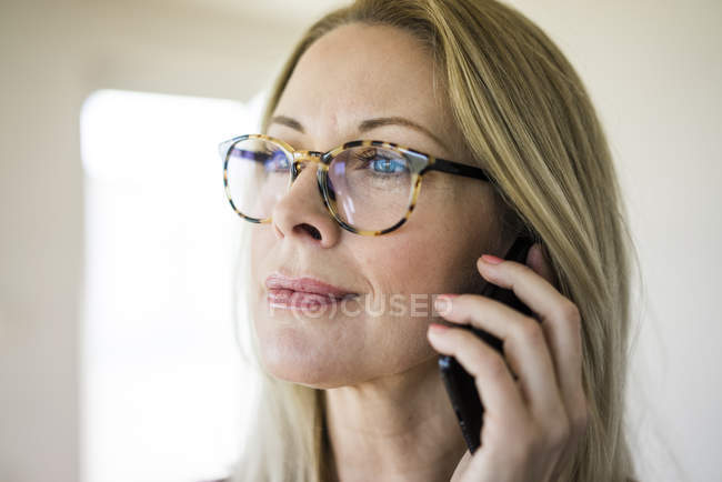 Portrait of blond mature woman wearing glasses on the phone — Stock Photo