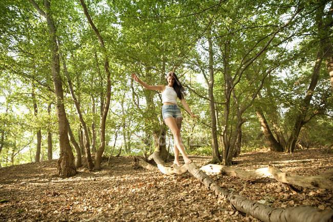 Jeune femme en forêt équilibrage sur une bûche — Photo de stock