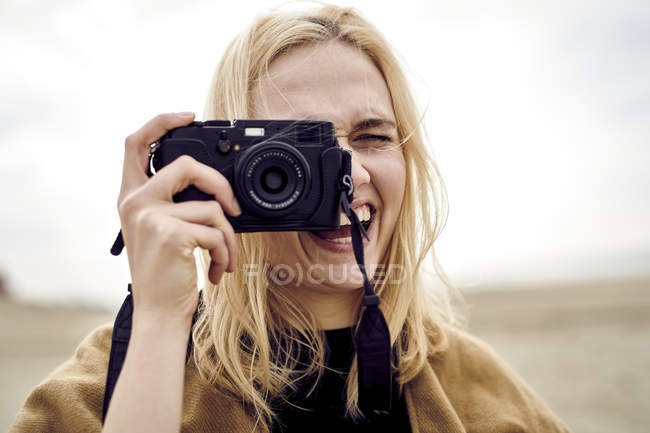 Portrait of blond young woman taking photo with camera on the beach — Stock Photo