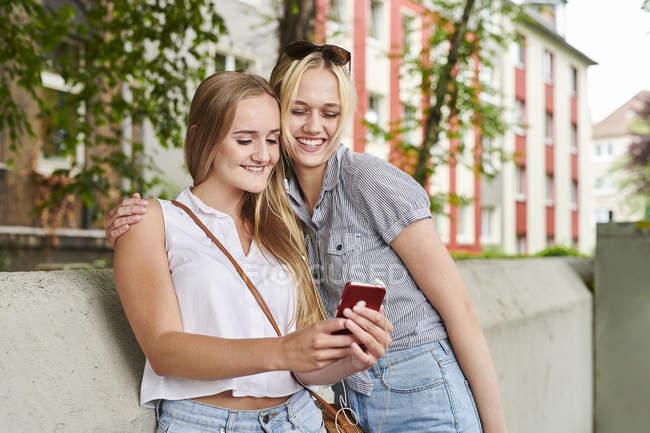 Duas jovens felizes compartilhando o telefone celular ao ar livre — Fotografia de Stock