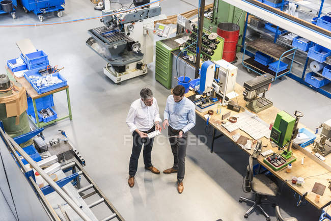 Businessmen during meeting with tablet in production hall, elevated view — Stock Photo