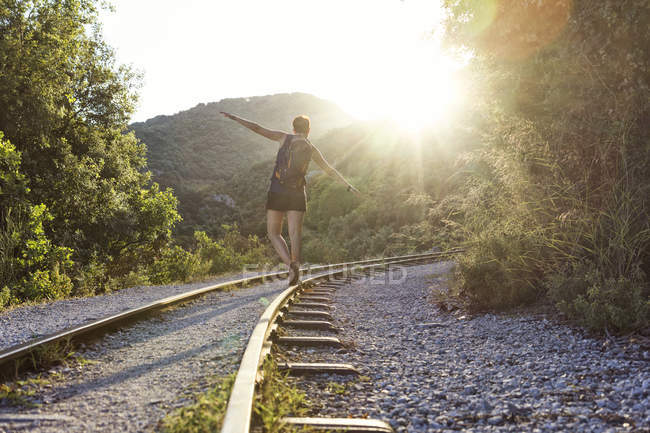 Greece, Pilion, Milies, back view of woman balancing along rails of Narrow Gauge Railway at sunset — Stock Photo