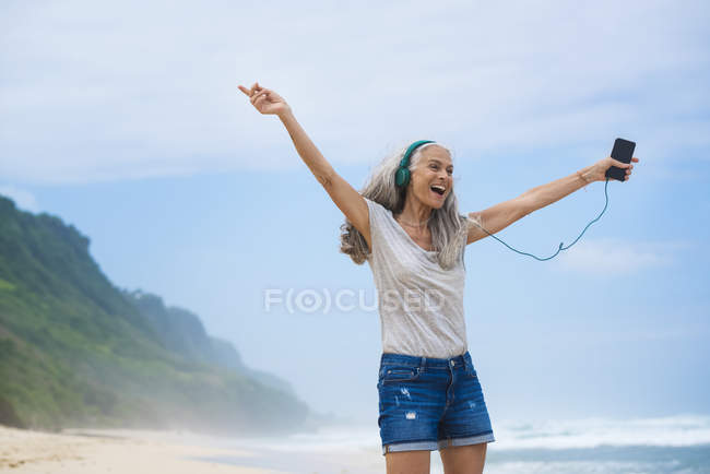 Senior woman with headphones dancing on the beach — Stock Photo