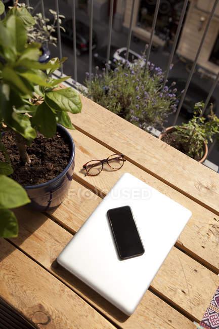 Smartphone, laptop y gafas en la paleta en el balcón - foto de stock