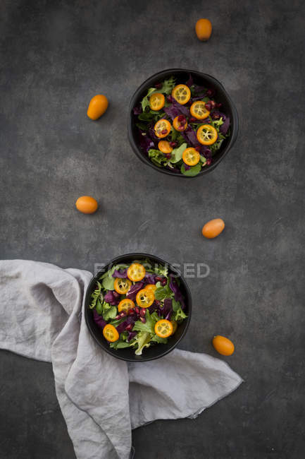 Bowl of mixed green salad with red cabbage, kumquat and pomegranate seeds — Stock Photo