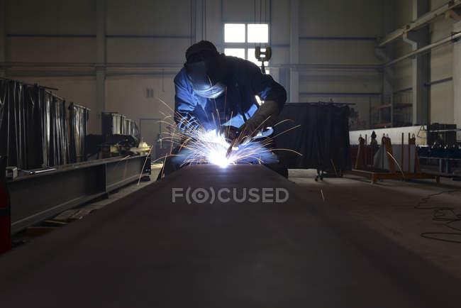 Сварщик за работой на заводе — стоковое фото