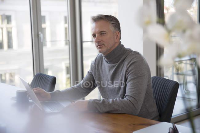 Businessmann mit Laptop im Konferenzraum — Stockfoto