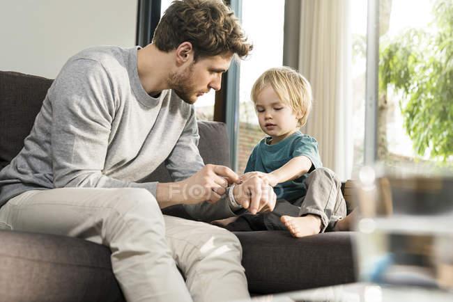 Син розглядає батьковий смарт-годинник на дивані вдома — стокове фото