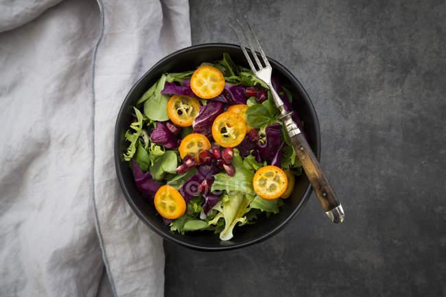 Cuenco de ensalada verde mixta con col roja, kumquat y semillas de granada - foto de stock