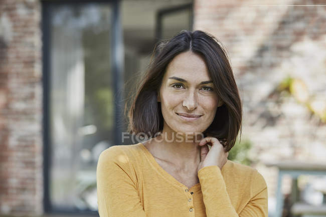Portrait of confident woman in front of her home — Stock Photo