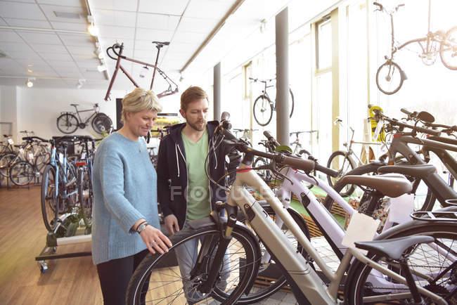 Vendedor ayudando al cliente con e-bike - foto de stock