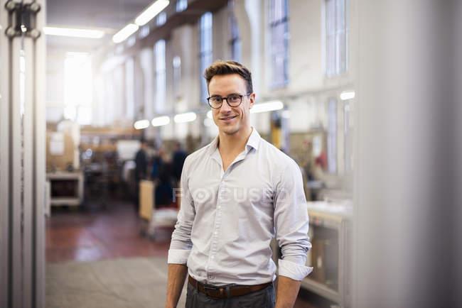 Ritratto di giovane uomo d'affari sorridente in fabbrica — Foto stock