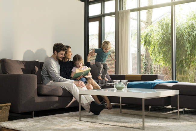 Family on sofa at home reading book with boy jumping — Stock Photo