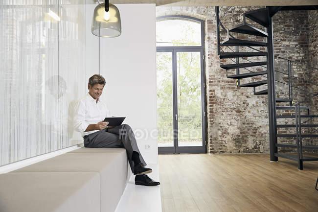 Бізнесмен сидить на лавці в сучасному офісі за допомогою планшета — стокове фото