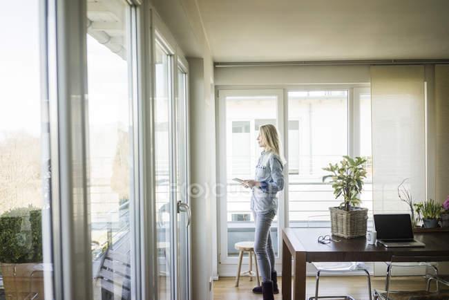 Mulher com tablet olhando pela janela — Fotografia de Stock