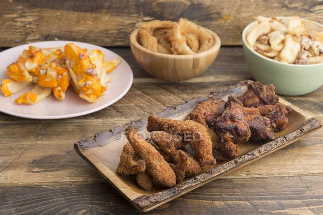 Типові американські продукти харчування, картопля з сиром і беконом, смажені Кільця цибулі і курячі крила — стокове фото