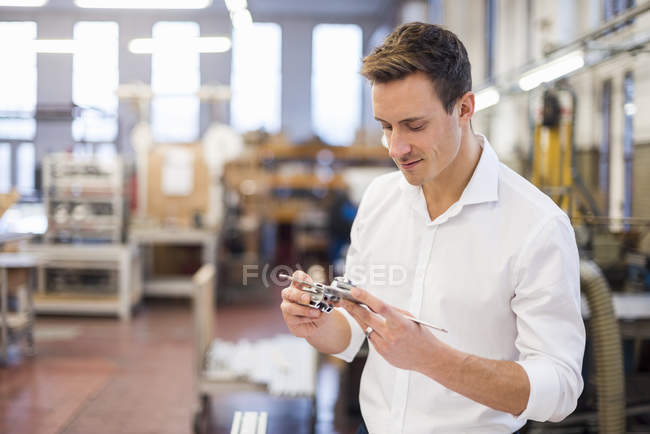 Young businessman in factory holding component — Stock Photo