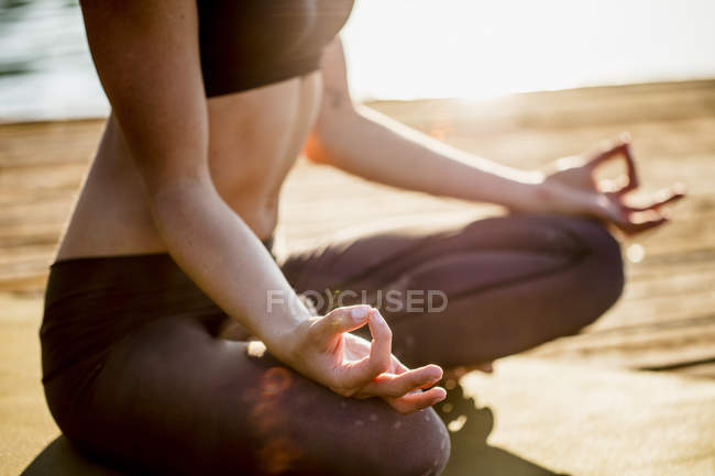 Close-up of woman practicing yoga on jetty at lake — Stock Photo