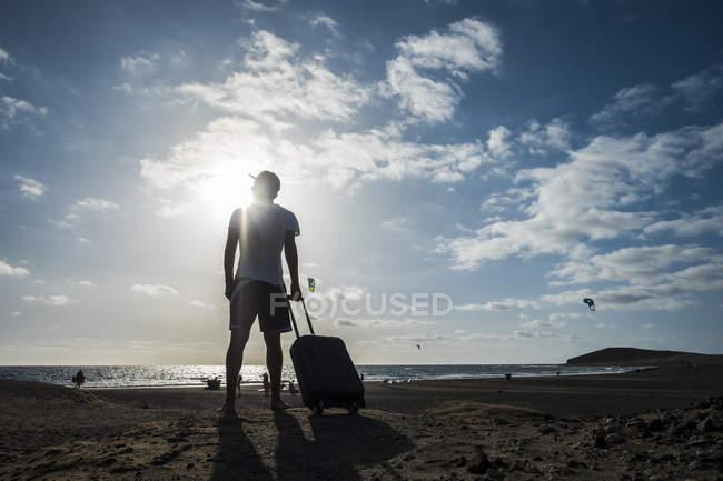Uomo in piedi con valigia rotolante in spiaggia — Foto stock