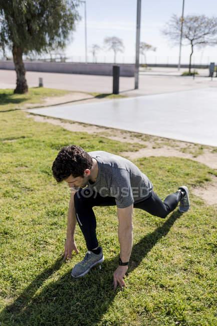 Спортивний чоловік, що тягнеться на луг — стокове фото