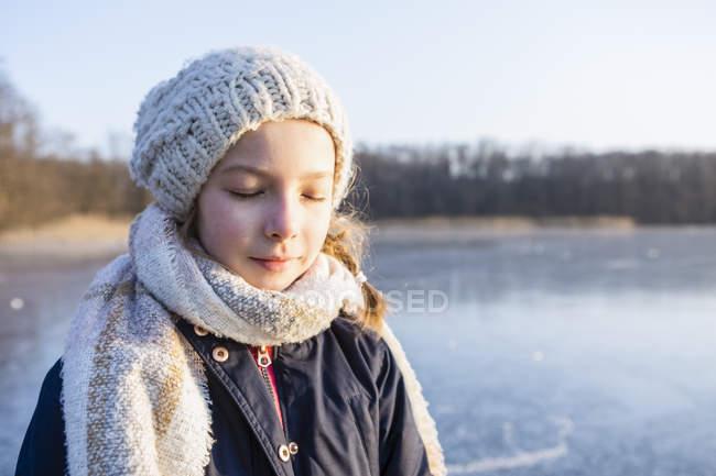 Deutschland, brandenburg, straussee, porträt eines mädchens auf gefrorenem see mit geschlossenen augen — Stockfoto