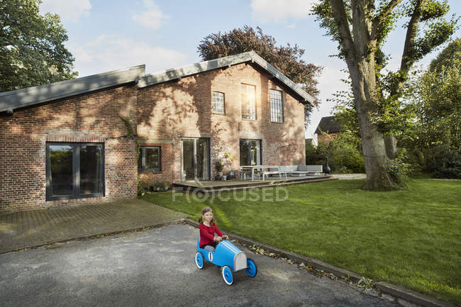 Girl playing with soapbox in driveway of residential house - foto de stock