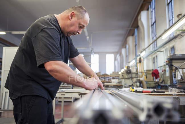 Людина на заводі, що працює на металевому компоненті — стокове фото