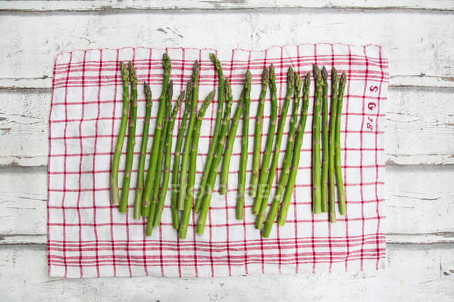 Organic green asparagus on red-white kitchen towel — Stock Photo