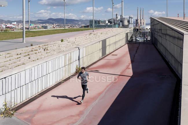 Homem esportivo correndo em um muro na cidade — Fotografia de Stock