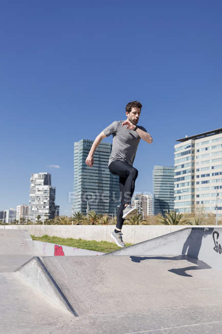 Sportive man jumping in a skatepark in the city — Stock Photo